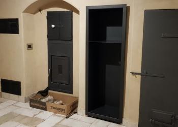 Akumulační kachlová kamna s teplovodním topeništěm Brunner napojeným na akumulační tah, přikládání a obsluha z chodby.