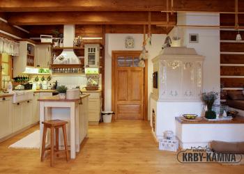 Kachlový sporák z ručně mačkaných a malovaných kachlů orientovaný do kuchyně ve světnici