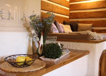 Kachlový sporák s ležením a dřevěnou lavicí je doplněn rustikální omítkou